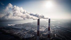 Inquinamento atmosferico da fumo che esce da due camini della fabbrica Siluetta dell'uomo Cowering di affari Immagini Stock