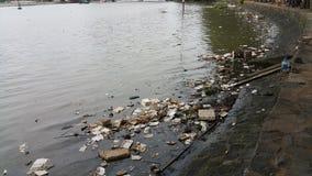 Inquinamento di plastica in acqua lungo la sponda del fiume fotografie stock