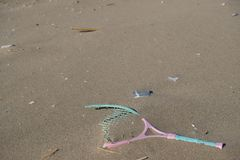 Inquinamento di plastica del mare della racchetta sull'ecosistema della spiaggia sabbiosa, immondizia sulla costa di mare immagini stock libere da diritti
