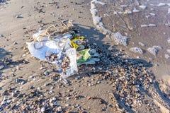 Inquinamento di plastica sulla riva, lavata dal mare Fotografia Stock
