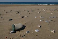 Inquinamento sporco del mare del contenitore di vetro sull'ecosistema della spiaggia sabbiosa, immondizia sulla costa di mare fotografie stock