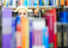 Inquiring look. Crazy stare behind the books Royalty Free Stock Photography
