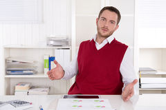 Inquiringly clerk with open hands at desk. Royalty Free Stock Photo