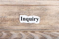 Inquiry text on paper. Word Inquiry on torn paper. Concept Image.  Stock Image