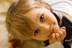 Inquisitive Boy. Closeup portrait of young boy with his head turned to the side, his chin resting on his hand.  Laying on his stomach Stock Image