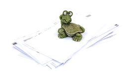 Inquisitive Hefty Turtle Paperweight Stack Bills. A small solid molded hefty turtle paperweight sitting on a stack of paid bills Stock Image