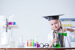 Inquisitive little girl pouring reagent into flask Stock Image