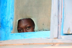 Inquisitive look through a window, Africa. A kid looks with curiosity through window hole at visitors in Mankessim, a small junction town between Accra and Cape Royalty Free Stock Image