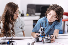 Inquisitive pupils exploring robot at school. Exploring new technologies. Curious attentive able children sitting at school and having science class while royalty free stock image