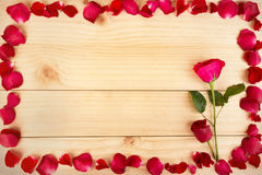 Inrama form som göras ut ur rosa kronblad på wood bakgrund, Valentin Royaltyfri Bild