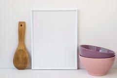 Inrama modellen på vit bakgrund, färgrika keramiska bunkar, den wood skeden, den utformade bilden för socialt massmedia Royaltyfri Foto