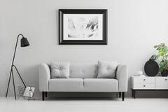 Inramat foto på en vägg ovanför ett infall, den gråa soffan med kuddar i en minimalist vardagsruminre och stället för en tabell V royaltyfri bild