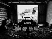 Inre är den lantliga ladugården med den motoriska odlaren Arkivfoto