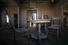 Inre av övergiven gammal västra byggnad med två gamla stolar och tabell arkivbilder