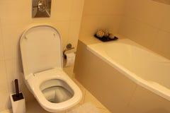 Inre av badrummet en toalettbunke och ett badkar fotografering för bildbyråer