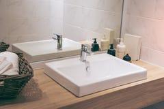 Inre av badrummet med den vaskhandfatvattenkranen och spegeln arkivbild