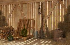 Inre av den gamla lantliga ladugården med baler av hö, vedträ, hjälpmedel för arbete Strålar av ljus till och med sprickorna inom Arkivfoto
