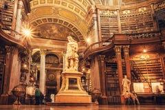 Inre av den historiska korridoren med skulpturer och bookshelfs av det österrikiska nationella arkivet Arkivbild