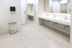 Inre av den offentliga rena toaletten i delad toalett där är ett brett val av vaskar med speglar Arkivbilder