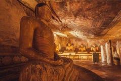 Inre av den 1st för århundrade grottatemplet F. KR. med sammanträde i meditationen Gautama Buddha och målat tak Royaltyfri Foto