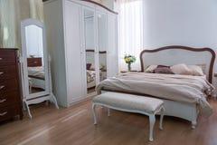 Inre av det hemtrevliga sovrummet med garderoben, säng och speglar i modern design royaltyfri fotografi