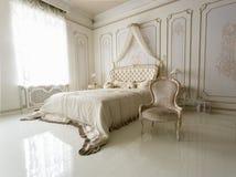 Inre av det klassiska vita sovrummet med stor säng och stol Arkivfoto