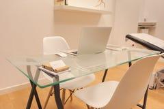 Inre av det minimalist kontoret med vita väggar, trägolv, trä och exponeringsglasdatortabell och vit bokhylla med mappar arkivbilder