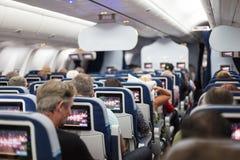 Inre av det stora kommersiella flygplanet med passagerare på platser som väntar till taik av Royaltyfri Fotografi