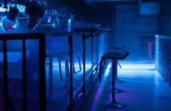 Inre av en bar med lynnig blå belysning Royaltyfri Fotografi