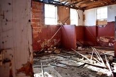 Inre av en gammal övergiven skola med väggar för röd tegelsten Arkivbild