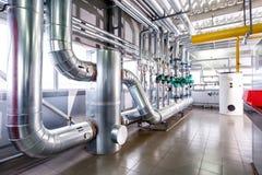 Inre av en industriell kokkärl, leda i rör, pumpar och bilar Arkivfoto