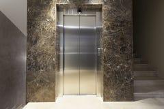 Inre av en korridor med passagerareelevator- och marmortrappa Arkivfoto