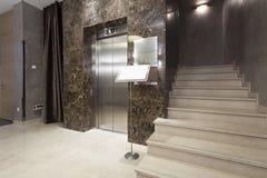 Inre av en korridor med passagerareelevator- och marmortrappa Arkivbild