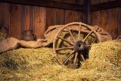 Inre av en lantlig lantgård - hö, hjul, kanna Fotografering för Bildbyråer