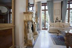 Inre av en vardagsrum med spisen i lyxig villa Royaltyfri Bild