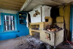 Inre av ett övergett ryskt lantligt hus, rysk ugn royaltyfria bilder
