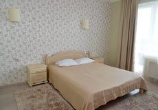 Inre av ett dubbelt hotellrum i ljus tonar med en dubbelsäng Royaltyfria Foton