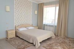 Inre av ett dubbelt hotellrum i ljus tonar med en dubbelsäng Royaltyfri Foto