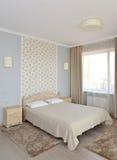 Inre av ett dubbelt hotellrum i ljus tonar med en dubbelsäng Arkivbilder