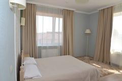 Inre av ett dubbelt hotellrum i ljus tonar med två fönster Arkivfoton
