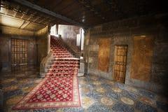 Inre av ett gammalt spanjorhus med röd matta, trappa och dörrar Royaltyfri Bild