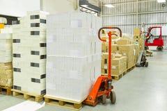 Inre av ett lager med manuell truc för gaffeltruckpalettutmatningsfack i efterbehandlaren Royaltyfri Fotografi