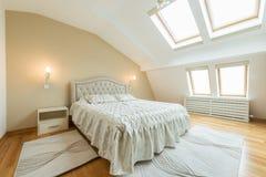 Inre av ett lyxigt vindsovrum med ledar- säng royaltyfri fotografi