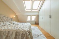 Inre av ett lyxigt vindsovrum med ledar- säng arkivbilder