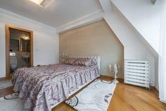 Inre av ett lyxigt vindsovrum med ledar- säng och badrummet arkivbilder