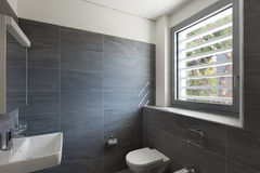 Inre av ett modernt hus, grått badrum royaltyfri bild
