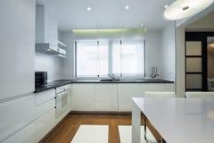Inre av ett modernt lyxigt ljust vitt kök Arkivbilder