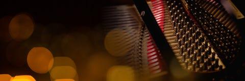 Inre av ett piano med gula ljus royaltyfri foto