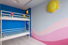 Inre av ett rum för barn` s för två flickor efter reparation, målad vägg och britssäng royaltyfri bild
