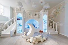 inre av ett rymligt rum för barn` s dekorativ slott med säng inom, den modiga glidbanan och trappa Royaltyfri Bild